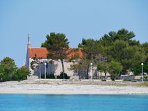 The Croatian island Premuda in the Mediterranean. The Krijal church with a graveyard situated at the local harbour on the small island Premuda in the Adriatic stock images