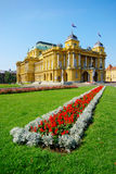 Croatian National Theater, Zagreb, Croatia. Building of Croatian National Theater (HNK) in Zagreb, Croatia on sunny summer day with flower, green grass and blue Stock Photos