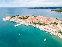Croatian town of Porec, shore of blue azure turquoise Adriatic Sea, Istrian peninsula, Croatia. Bell tower, red tiled roofs. Croatian town of Porec, shore of royalty free stock photography