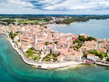 Croatian town of Porec, shore of blue azure turquoise Adriatic Sea, Istrian peninsula, Croatia. Bell tower, red tiled roofs. Croatian town of Porec, shore of stock photography