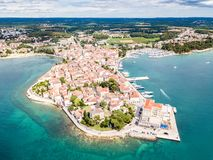 Croatian town of Porec, shore of blue azure turquoise Adriatic Sea, Istrian peninsula, Croatia. Bell tower, red tiled roofs. stock photos