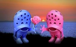 Croc在日落的鞋子浪漫史 免版税库存图片