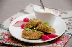 Crocchette con il merluzzo della crusca con panna acida e i radis Immagine Stock Libera da Diritti
