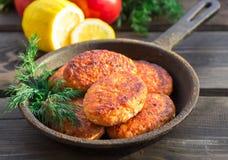 Crocchette di pesce di color salmone in padella, pomodori e limone del ghisa Fotografie Stock