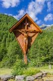 Croce cattolica di legno accanto alla strada su un fondo delle alpi verdi Fotografie Stock