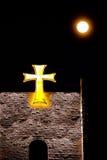Croce celtica sul castello sotto la luna piena Fotografie Stock
