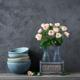 Crocery and roses bouquet Stock Photography