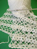 Crochet. White crochet, threads and hook on the green background Stock Photos