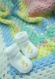 Crochet Baby Blanket and Booties. Pastel coloured, crocheted baby blanket with white booties that have yellow embroidered chicks on them Royalty Free Stock Photos