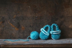 Crochet Baby Booties. With blue yarn on a wooden shelf royalty free stock images