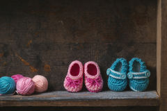 Crochet Baby Booties. With knitting yarn on a wooden shelf royalty free stock image