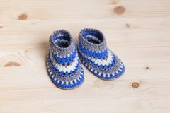 Crochet Baby Booties on wooden background. Cute Handmade blue Baby Booties Crochet on wooden background Royalty Free Stock Photos