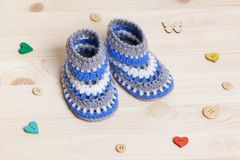 Crochet Baby Booties on wooden background. Cute Handmade blue Baby Booties Crochet on wooden background with wooden buttons stock photo