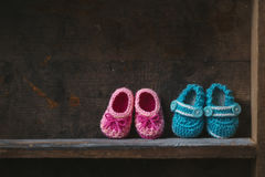 Crochet Baby Booties. On a wooden shelf royalty free stock photos