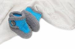 Crochet baby boy booties. Blue and gray crochet baby boy booties on white crochet blanket Stock Photography