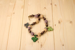 Crochet baby handmade beads with acorns and leaves on a wooden t Royalty Free Stock Image