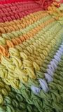 Crochet blanket in puff stitch. Comfortable, cosy and colourful wool blanket in red, orange, green and grey stock image
