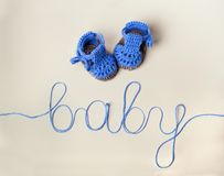 Crochet Blue Baby Booties on gray background. Handmade cute  Blue Baby Booties Crochet on gray background Stock Photos