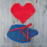 Crochet booties and heart. Stock Images