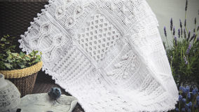 Crochet, Cable Knit Afghan Baby Blanket in White. Cable Knit Afghan Crochet Baby Blanket in White on Sofa with Lavender, closeup Soft Focus High Contrast royalty free stock images