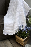 Crochet Cable Knit Afghan Baby Blanket in White. Cable Knit Afghan Crochet Baby Blanket in White on Sofa with Lavender, Soft Focus High Contrast Desaturated stock photography
