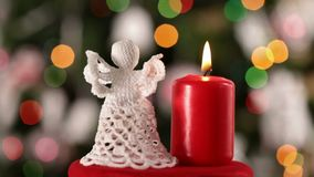 Crochet christmas angel decoration and burning candle spinning stock video footage