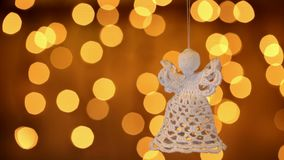Crochet christmas angel decoration hanging against blurry lights stock video