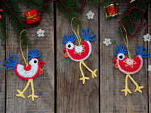 Crochet christmas decorations cockerels on wooden background.  Royalty Free Stock Images