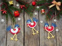 Crochet christmas decorations cockerels on wooden background.  Stock Photos