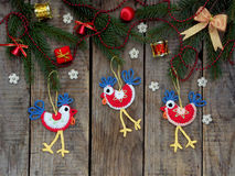 Crochet christmas decorations cockerels on wooden background.  Royalty Free Stock Photography