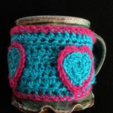 Crochet coffee mug warmer. Handmade cozy for your cup with button and heart mugwarmer Stock Photography