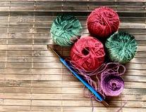 Crochet d'or pour le tricotage et les boules multicolores Tricotage de mamie métiers faits maison Image libre de droits