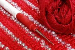 Crochet de crochet sur le knit de couleur rouge avec la décoration Photo stock