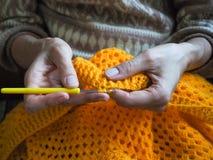 crochet De vrouw haakt geel garen op de donkere achtergrond Close-up van de handen Stock Foto