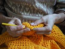 crochet De vrouw haakt geel garen op de donkere achtergrond Close-up van de handen Stock Afbeeldingen