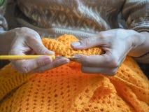 crochet De vrouw haakt geel garen op de donkere achtergrond Close-up van de handen Royalty-vrije Stock Foto's