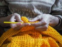 crochet De vrouw haakt geel garen op de donkere achtergrond Close-up van de handen Stock Afbeelding