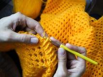 crochet De vrouw haakt geel garen op de donkere achtergrond Close-up van de handen Stock Fotografie