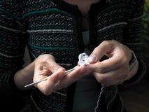 crochet De vrouw haakt wit garen op de donkere achtergrond Close-up royalty-vrije stock foto's