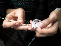 crochet De vrouw haakt wit garen op de donkere achtergrond Close-up royalty-vrije stock afbeelding
