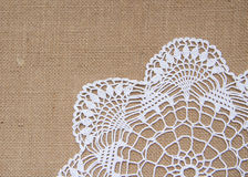 Crochet doily over burlap royalty free stock image