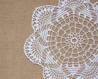 Crochet doily over burlap royalty free stock photography