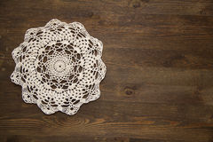 Crochet doily over dark wood Royalty Free Stock Photos