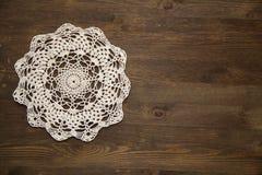 Crochet doily over dark wood. Cream Crochet doily over dark wood Royalty Free Stock Photos