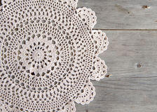 Crochet doily over old grey wood Stock Images