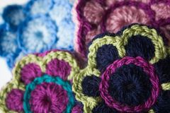 Crochet flowers in different colours. Crochet flowers made with different color wool. Shot in a studio Stock Photos