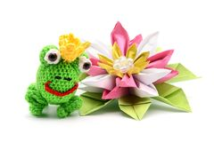 Crochet frog king with crown and origami water lily on white bac. Crochet frog king fairytale with crown and origami water lily on white background. tinker Royalty Free Stock Images