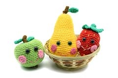 Crochet fruits apple pear and strawberry with smiling face on wh Stock Photos