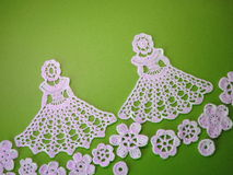 Crochet girls and flowers. Two white crochet girls and flowers on green background Royalty Free Stock Photos