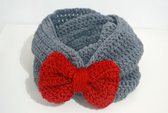 Crochet grey infinity scarf with red bow Royalty Free Stock Photos